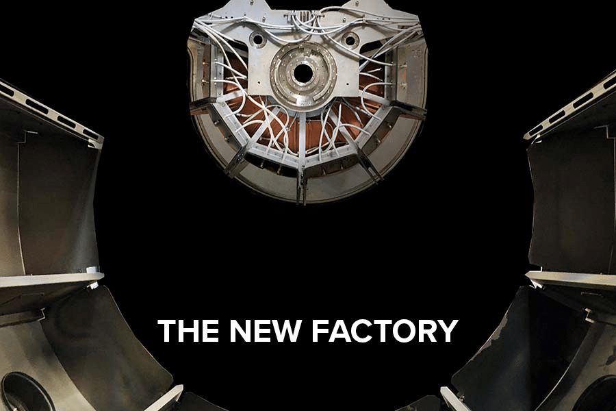 """Close-up of a sputter machine. White text with """"The new factory""""."""