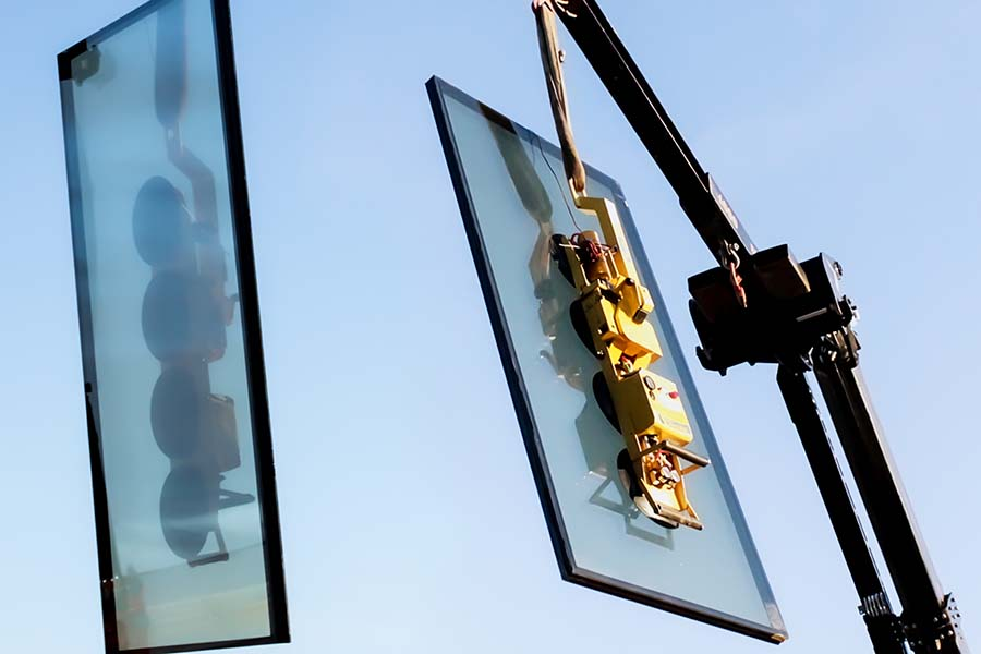Crane lifting a dynamic glass in the air on a sunny day