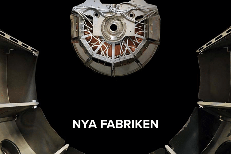 """Close-up of a sputter machine. White text with """"Nya fabriken""""""""."""