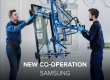"""Two men working on dynamic glass in the factory. White text says """"New Co-operation""""."""