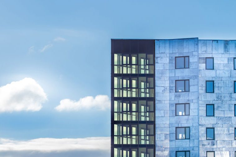 Residential building Knäckepilen in Uppsala Sweden. Sunny background with a light blue building with ConverLight Dynamic Glass.