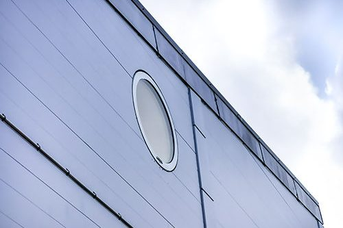 Outside view of a grey facade with a round solar powered smart glass.