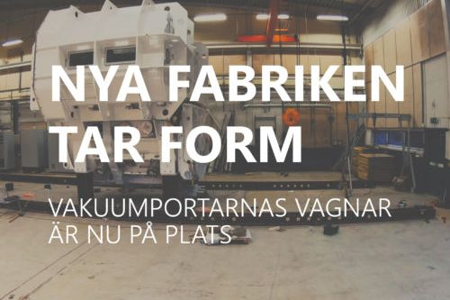 """Cover photo for a news update with the text """"Nya fabriken tar form. Vakuumportarnas vagnar är nu på plats."""" The text is white over a picture of the delivery."""